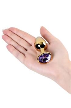 Золотистая коническая анальная пробка с фиолетовым кристаллом - 7 см.